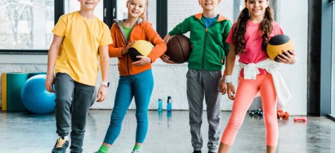 dzieci na sali gimnastycznej trzymające sprzęt sportowy na zajęcia wychowania fizycznego